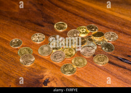 Several dozen gold coins, mostly 19th century 20 Francs coins from Switzerland, piled up on a wooden table. - Stock Photo
