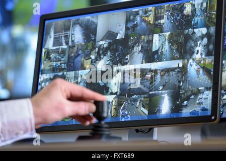 Close up of hand on camera control joystick in control room with video wall - Stock Photo
