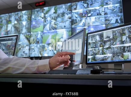 Detail of hand on camera control joystick in control room with video wall - Stock Photo