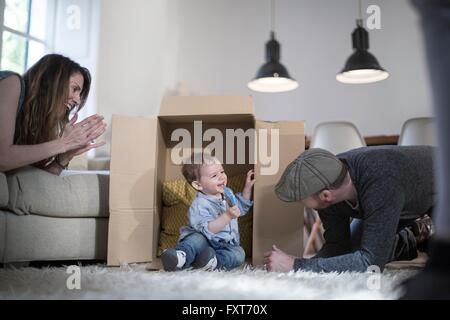 Parents playing with baby boy and cardboard box - Stock Photo