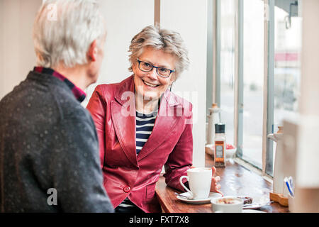 Senior couple chatting in cafe window seat - Stock Photo