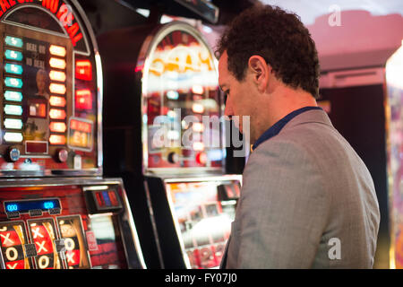 man gambling in casino with fruit machines losing money - Stock Photo