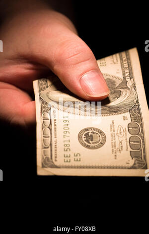A man's right hand emerging from the shadows holding out a $100 bill - Stock Photo