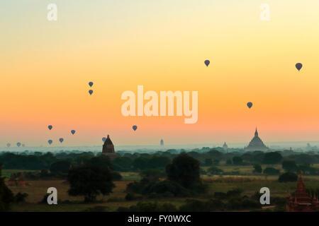 View of Ananda Phaya over Old Bagan and temples with hot air balloons at dawn, Myanmar (Burma) - Stock Photo