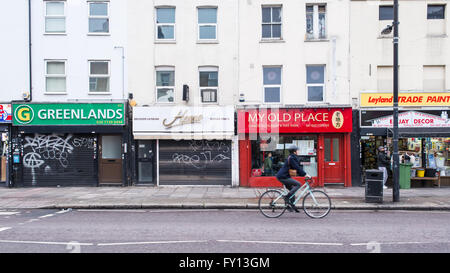 Typical street with small independent retail shops in London East End. Cyclist passing by on the road. - Stock Photo