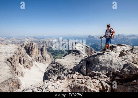 Mountaineer ascending of the Piz Boé on the Vallonsteig in the Sella group, behind the Val Badia with Heiligkreuzkofel - Stock Photo