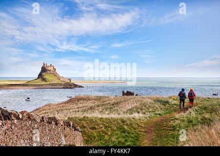 Hikers walking on the Lindisfarne Heugh, Holy Island, Northumberland, England, UK - Stock Photo