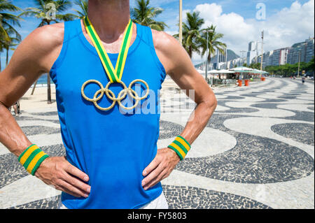 RIO DE JANEIRO - MARCH 10, 2016: Athlete stands with Olympic rings gold medal on the Copacabana Beach boardwalk. - Stock Photo