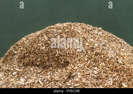 Mound of wood chippings bark to be used as a mulch on a garden flower bed or border. - Stock Photo
