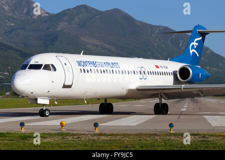 Montenegro Airlines Fokker 100 vacates runway 32 at Tivat airport. - Stock Photo