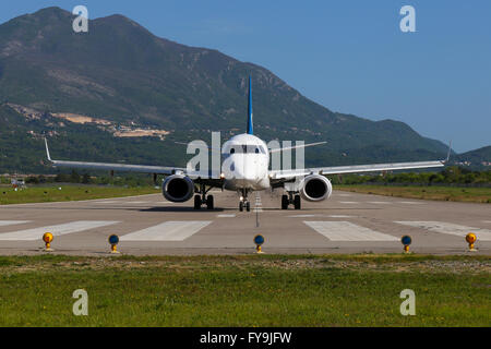 Montenegro Airlines Embraer 190 vacates runway 32 at Tivat airport. - Stock Photo