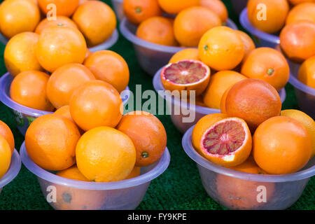 Market stall selling blood oranges in plastic bowls - Stock Photo