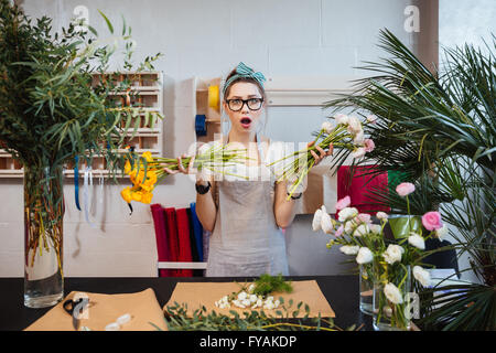 Amazed shoked young woman florist designing bouquet and holding two bunches of flowers - Stock Photo