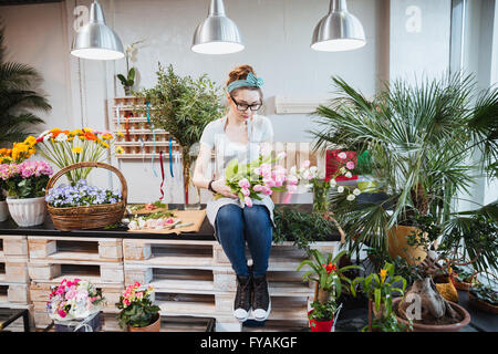 Cute lovely young woman florist sitting and arranging pink tulips in flower shop - Stock Photo