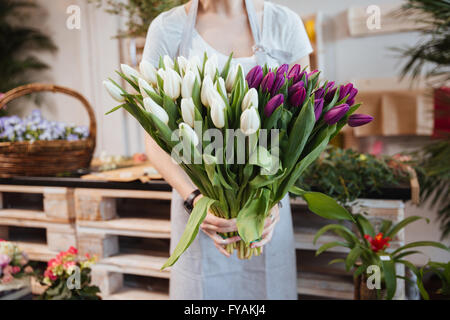 Closeup of young woman florist standing and holding bouquet of tulips in flower shop - Stock Photo