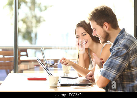 Side view of two young adult students studying and talking about lessons comparing together laptop information in - Stock Photo