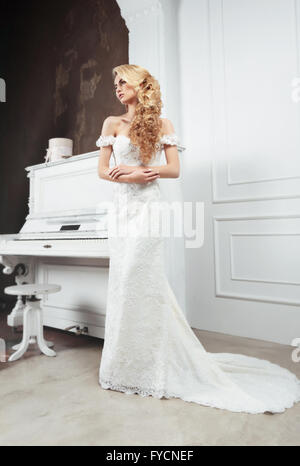 The bride in a long dress with a train. Long light hair. Wedding hairstyle. - Stock Photo