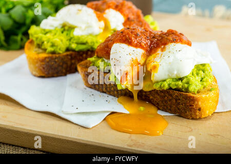 Avocado Toast with poached eggs on cutting board - Stock Photo