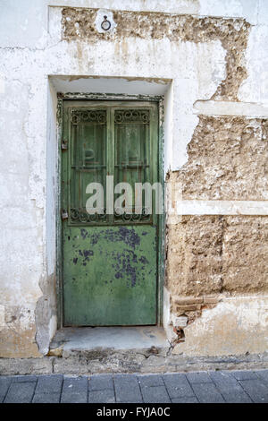White wall with texture, green wooden door - Stock Photo