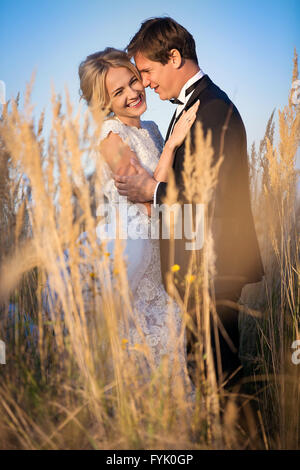 Young wedding couple standing in a field - Stock Photo