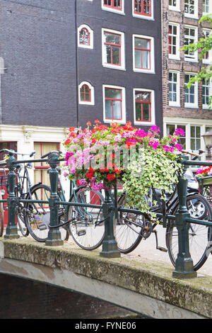 Bridge over canal in Amsterdam. Bicycles are standidg on the bridge. The bridge is decorated with flowers. - Stock Photo