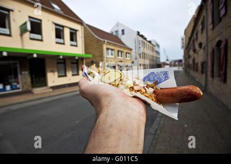 hand holding a hotdog in a bun - Stock Photo