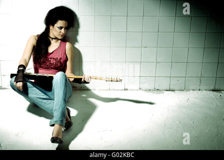Punk Girl playing guitar on an underground background high contrast - Stock Photo