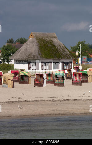 Beach chairs and thatched-roof house on beach - Stock Photo