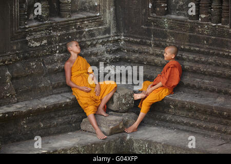 Young Buddhist monks at Angkor Wat (12th century Khmer temple), Angkor World Heritage Site, Siem Reap, Cambodia - Stock Photo