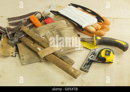 Old and worn carpentry tools placed on wooden pla - Stock Photo