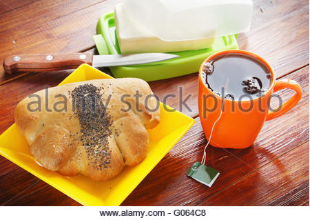 Freshly baked bun and cup of black tea for breakfast - Stock Photo