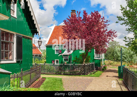 Green wooden houses with red roofs in small village of Zaanse Schans, Netherlands. - Stock Photo