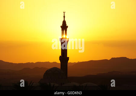 sunset over mosque in egypt town of el quesir - Stock Photo