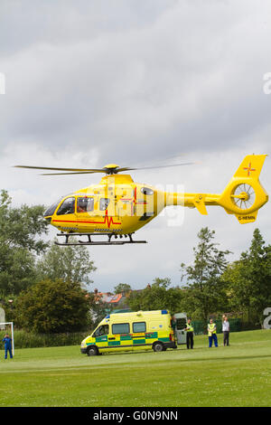 East Anglia Air Ambulance taking off from a field containing a road ambulance - Stock Photo