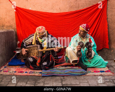 Two gnawa musicians in the narrow streets of the Medina of Marrakesh - Stock Photo