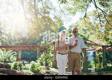 Portrait of couple of senior tourist walking through a park on a summer day. mature couple on a vacation. - Stock Photo