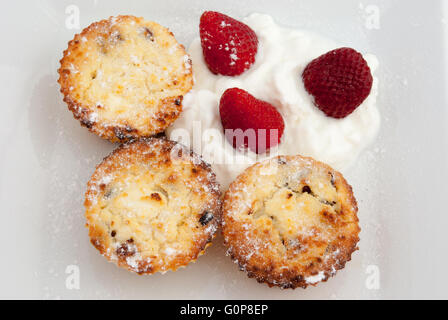Cottage cheese syrniki, baked as cupcakes or muffins, served with yogurt and strawberries on the white plate closeup. - Stock Photo