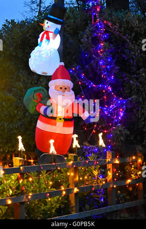 Illuminated Xmas decorations including Father Christmas along the front garden fence of a residential property Brentwood - Stock Photo