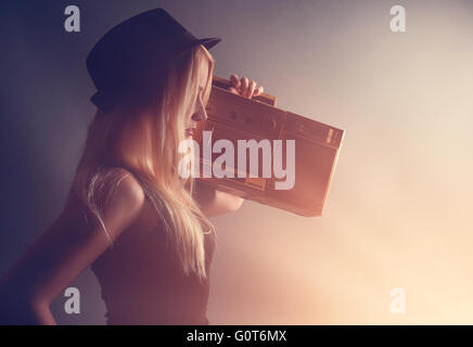 A blonde hipster girl is listening to a vintage gold boombox radio with a speaker for a music entertainment concept. - Stock Photo
