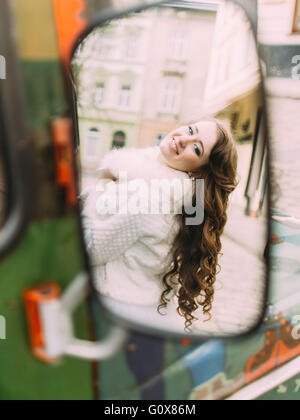 Reflection of pretty young woman wearing fur cape in the rearview mirror - Stock Photo