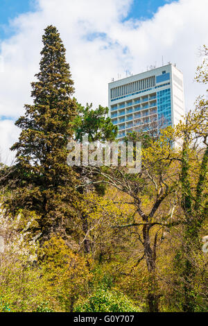 Facade of high-rise hotel building behind trees on mountainside - Stock Photo