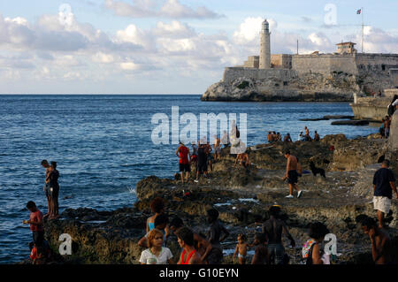 Local people along the famous Malecon on the waterfront in the Old City of Havana. Castillo de los Tres Reyes del - Stock Photo