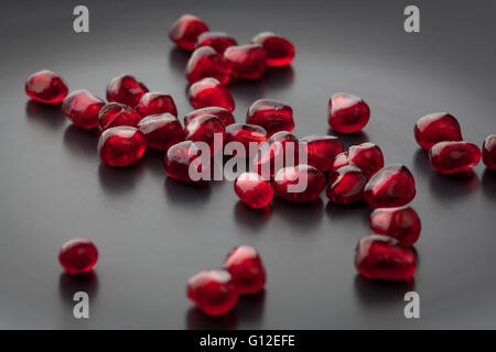 Pomegranate seeds scattered on black plate extreme closeup. Shallow depth of field. - Stock Photo