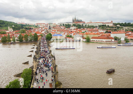 View of a crowded Charles Bridge, River Vltava, Prague Castle and St Vitus Cathedral, Prague from Charles Bridge - Stock Photo