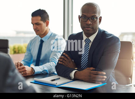 Executive multiracial business team having a meeting in the office with focus to a serious middle-aged African American - Stock Photo