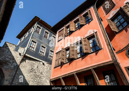 Close up bottom view of brown and blue historical buildings in Plovdiv old town, on bright blue sky background. - Stock Photo