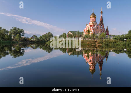 Russian orthodox church in Almaty, Kazakhstan known also as Church of Exaltation of the Holy cross, and its reflection - Stock Photo