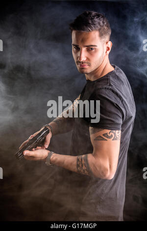 Young handsome man holding a hand gun, wearing black t-shirt, on dark background in studio - Stock Photo