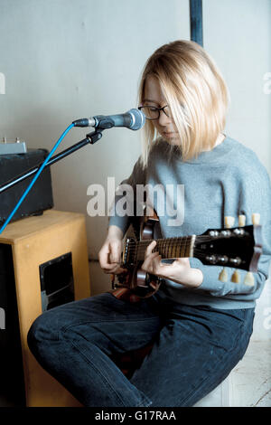 Young woman playing guitar and singing microphone - Stock Photo
