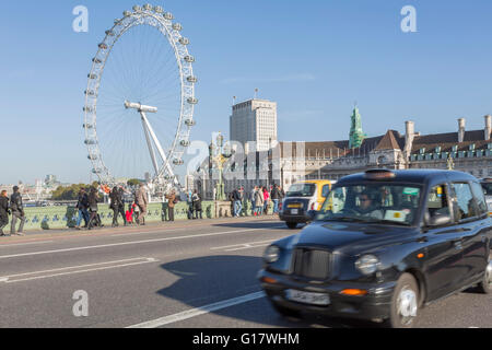 Black cab and crowd of people crossing Westminster Bridge in London with London Eye in the background - Stock Photo